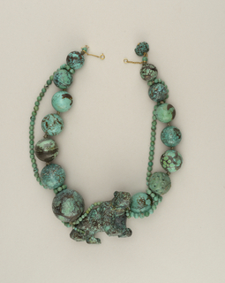 Necklace composed of large spherical turquoise beads, a string of smaller turquoise beads, a gold chain, and a large carved bear in turquoise with diamond collar and rubies for eyes; large textured carved turquoise bead with diamonds.