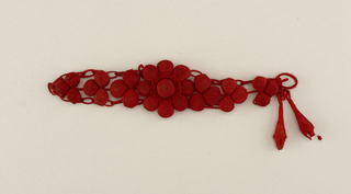 A red colored bracelet made of weaved balls, with a centered flower, dangling two tear drop shapes at the end. Part of a set.