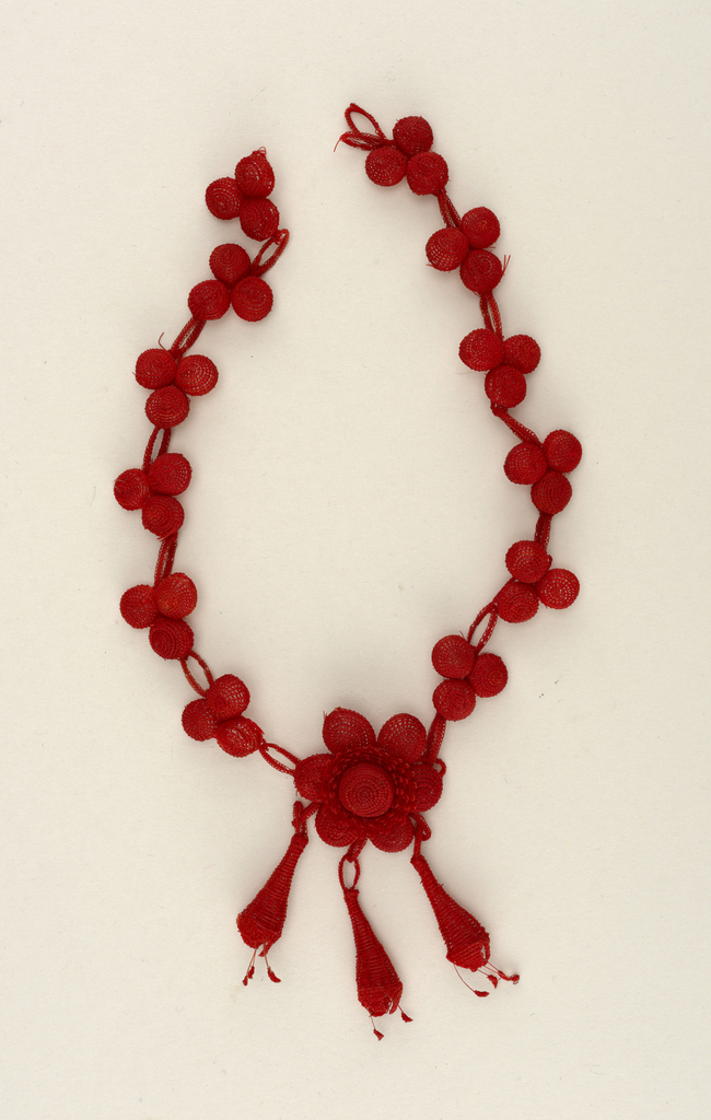 A red colored necklace made of weaved balls in threes, with a centered flower, dangling three teardrop shapes. Part of a set.