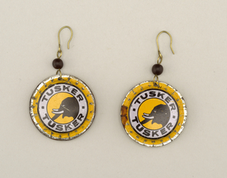 """Each earing a slightly flattened bottle cap showing a black elephant head in profile within a white circular band with """"Tusker"""" above and below, all on a yellow ground; suspended from shaped wire with one black glass bead."""