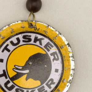 "Each earing a slightly flattened bottlecap showing a black elephant head in profile within a white circular band with ""Tusker"" above and below, all on a yellow ground; suspended from shaped wire with one black glass bead."
