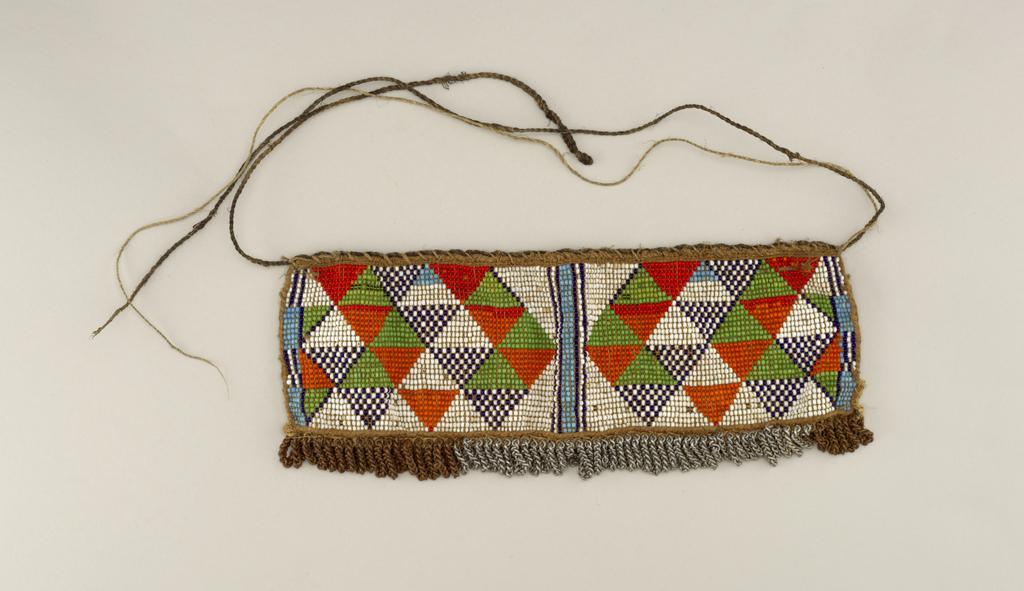 Rectangular panel of beadwork, predominantly red, green, blue, white; row of metal chain links bottom edge; fiber ties.