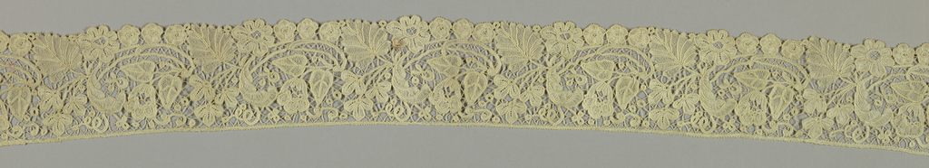 Duchesse style lace with a pattern of flowers, buds and leaves.