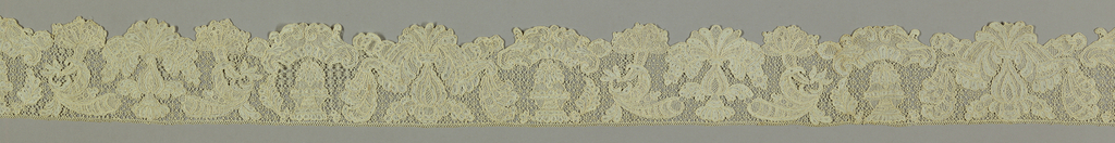 Scalloped border with foliated and floral forms.
