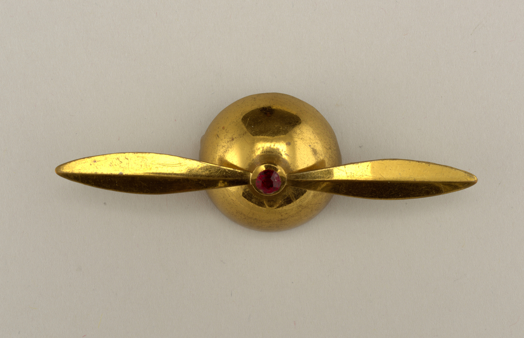 Brooch in shape of airplane propellor.