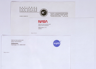 Above, logo at center with double line and text on either side. Central logo printed in black of two spheres in star-filled sky, with partial lines of orbit and delta wing around the larger sphere; surrounding image is printed: NATIONAL AERONAUTICS AND SPACE