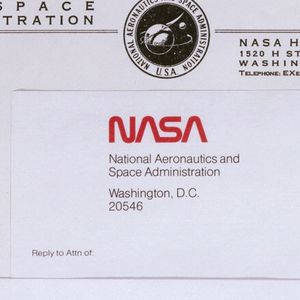 Above, logo at center with double line and text on either side. Central logo printed in black of two spheres in star-filled sky, with partial lines of orbit and delta wing around the larger sphere; surrounding image is printed: NATIONAL AERONAUTICS AND SPACE ADMINISTRATION U.S.A.; upper left: NATIONAL/AERONAUTICS/AND SPACE/ ADMINISTRATION. To lower right of central logo, address and telephone number. At left of logo, IN REPLY REFER TO.
