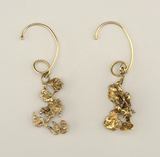 Each earring has large loop (for hooking around back of ear), attached to irregular cast gold pendent.