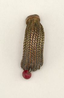 Curved band of inter-woven copper and brass wires with red glass bead at bottom, flat disk-like terminal at top.