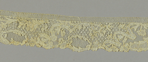 Band with a design of floral and foliated sprays balanced by ribbons and elaborate filling stitches.