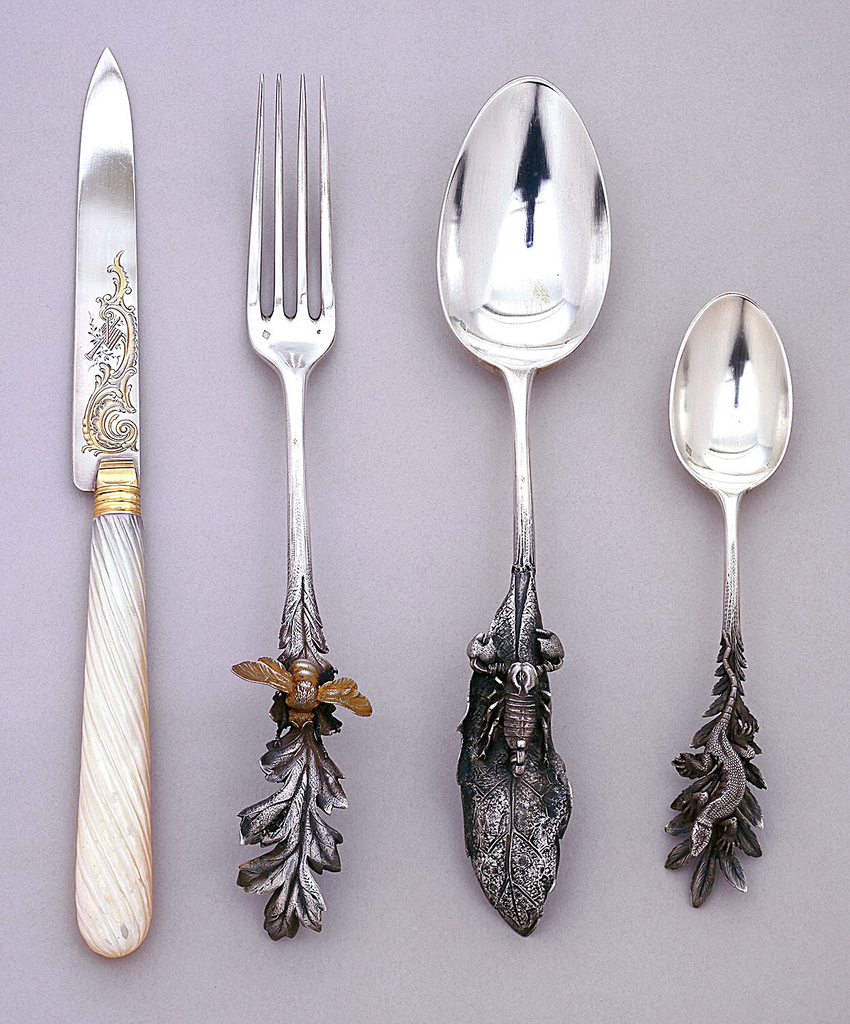 Dessert spoon with handle design of a scorpion on a leaf.