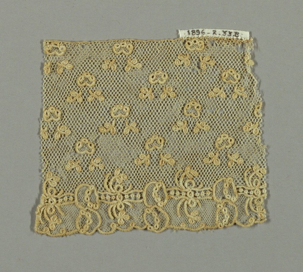 Alençon-style fragment with minute powdered floral design. Hexagonal mesh reinforced with buttonhole stitches (brides tortillées).