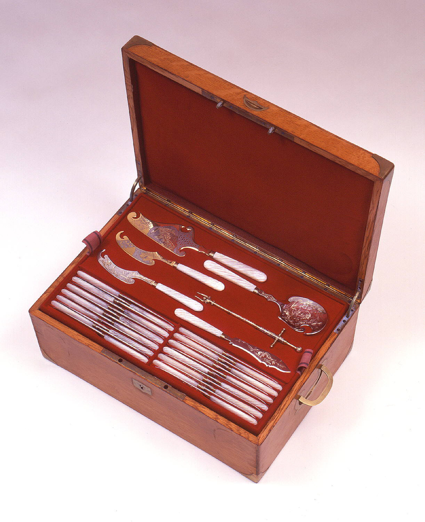 Rectangular box (a) with lock and hinged lid containing lined trays (b/d) and base, all with shaped cavities for storing cutlery; key with paper tag (e); shield-shaped brass cartouche on lid with conjoined, scrolling, foliate initials, J.N. or N.J.
