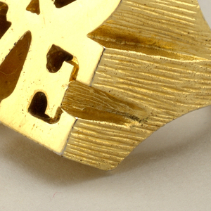 "Circular gilt metal ring with ""LO / VE"" in thick sculptural block letters."