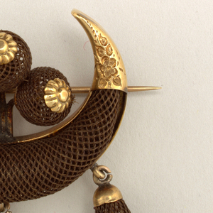 "Brooch consisting of a wide ""U"" shaped piece made out of woven brown hair capped at the ends with gold. Within the ""U"" shape are three balls of woven hair; hanging from the ""U"" are three teardrop shaped pendants of woven brown hair, accented with gold hardware."