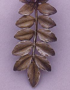 Dessert fork with red enameled bug on a gilded compound leaf.
