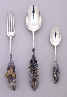 Dessert spoon with chameleon capturing a fly on a fern frond.