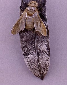 Handle in the form of a gilded honeybee with wings partially extended, on a leaf.