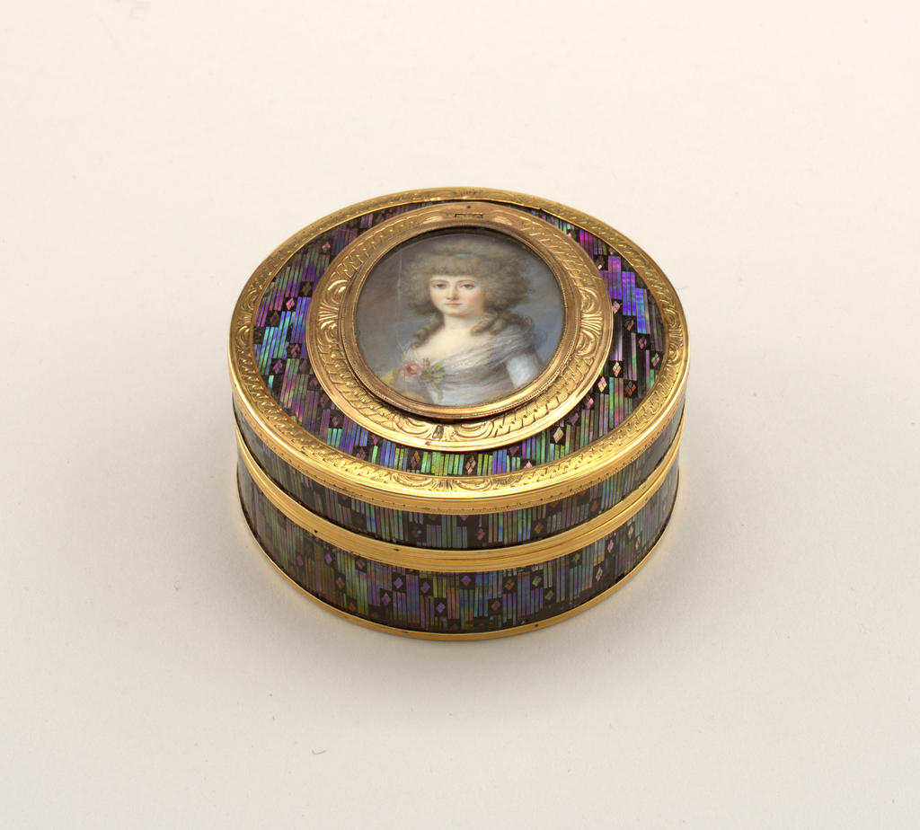Box, circular, with detachable cover; black lacquer on papier maché inlaid with all-over diaper design in mother-of-pearl with green, blue and purple iridescence; on cover, within gold frame, a hinged oval miniature of a lady in a blue gown, on ivory under glass; a concealed spring releases this and discloses a hidden miniature of a man with powdered hair wearing the blue ribbon of an order and an ermine bordered red robe, painted on ivory, under glass in a very narrow gold frame; border of cover and of main miniature gold engraved with guilloche design; plain molded gold rims; box and cover lined with tortoiseshell.