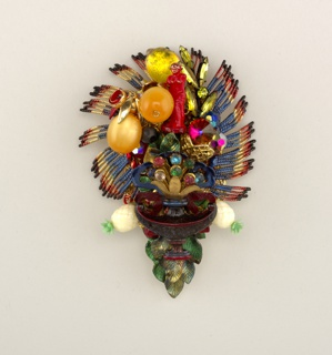 Inverted ovoid form composed of various media and costume jewelry fragments: colorful cast metal fringe-like surround, small red figure of Venus, plastic globes suggesting oranges, colored beads and glass pastes, central metal fleur-de-lys, plastic white pineapples, and glass leaves.