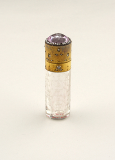 Crystal perfume bottle, oval in plan, straight-sided, with gold fittings hinged lid topped by oval faceted pink sapphire surrounded by 35 small diamonds, stylized flower pattern, flowers arranged in vertical rows, etched in crystal, pattern continued in gold, with 33 diamonds set in leaves and blossoms.