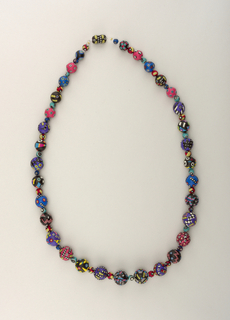Strand of beads all painted with colorful faces and patterns.