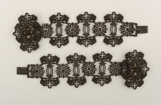 Pair of open ironwork bracelets, each one a wide, flexible, linked band formed of three quatrefoil-and-foliate forms alternating with rosettes, all in the Gothic style; simple rectangular clasp at one end; quatrefoil-and-foliate form with rosette on oval panel at other end, to receive clasp.