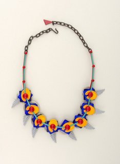 Eight linked movable elements; each composed of a spiral, leaf form, square, easel-shaped form; three plain links and short section of chain links at either end; hook on one end, triangular charm at other; bright enamel colors.