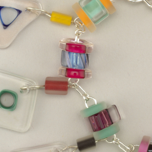 Colored and clear glass charms in various geometric shapes linked by silver chain; hook and loop, safety chain.