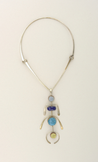 A two piece solid silver necklace with silver rings joining the pieces. Hanging from the center on its own silver piece are three blue pieces and one tan piece with small silver leaf like details on either side of the colors.