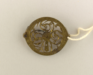 Oval. Pierced vertical center with four foliated scrolls forming a quatrefoil. Engraved border.