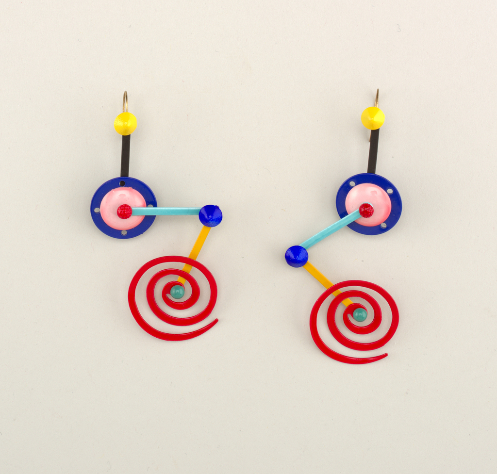 Earrings composed of hinged components: yellow circular post attached to black bar, a circle in blue and pink, another bar in light blue, then one in mustard yellow culminating in a red spiral.