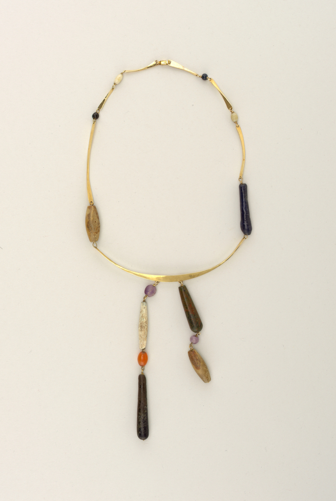 """Chain"" made of connected beads and flat thin strips of gold with one larger strip and the lower section from which hang the connected bead pendants."
