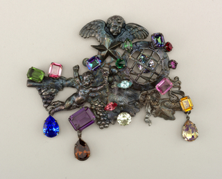 A brooch with an abstract composition made up of angles, ivy, and other shapes in a metallic blue. Hanging off the brooch are colorful stones in a variety of geometric cuts.