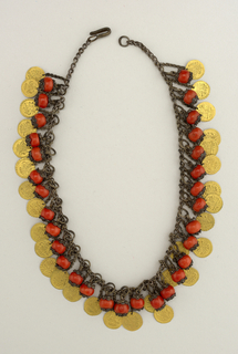 Silver chain with pendants of coral set in silver filigree alternating with gold disks.