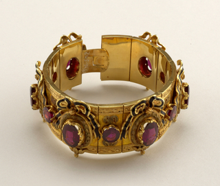 Articulated bracelet with clasp; design of oval garnets set in frames with ornament belwo and bow knot above, alternating with round garnets and gold ornaments, bands engraved in leaf-design at either side of the bracelet.
