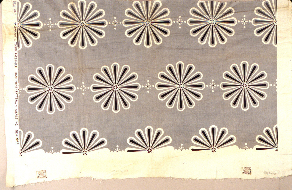 Pattern printed in grey and black of medallions formed by a small circle and petals radiating from the center.