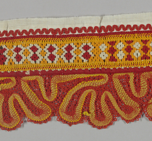 Red and yellow band of with drawn work with a scalloped bobbin lace border in a provincial pattern. Trimmed with red rick-rack on white cotton.