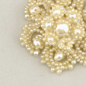 -41a and b: Circular ornament of central pearl surrounded by eight pearl clusters; below, and attached by four strings of seed pearls, is an ornament of central pearl with six radiating scrolls.