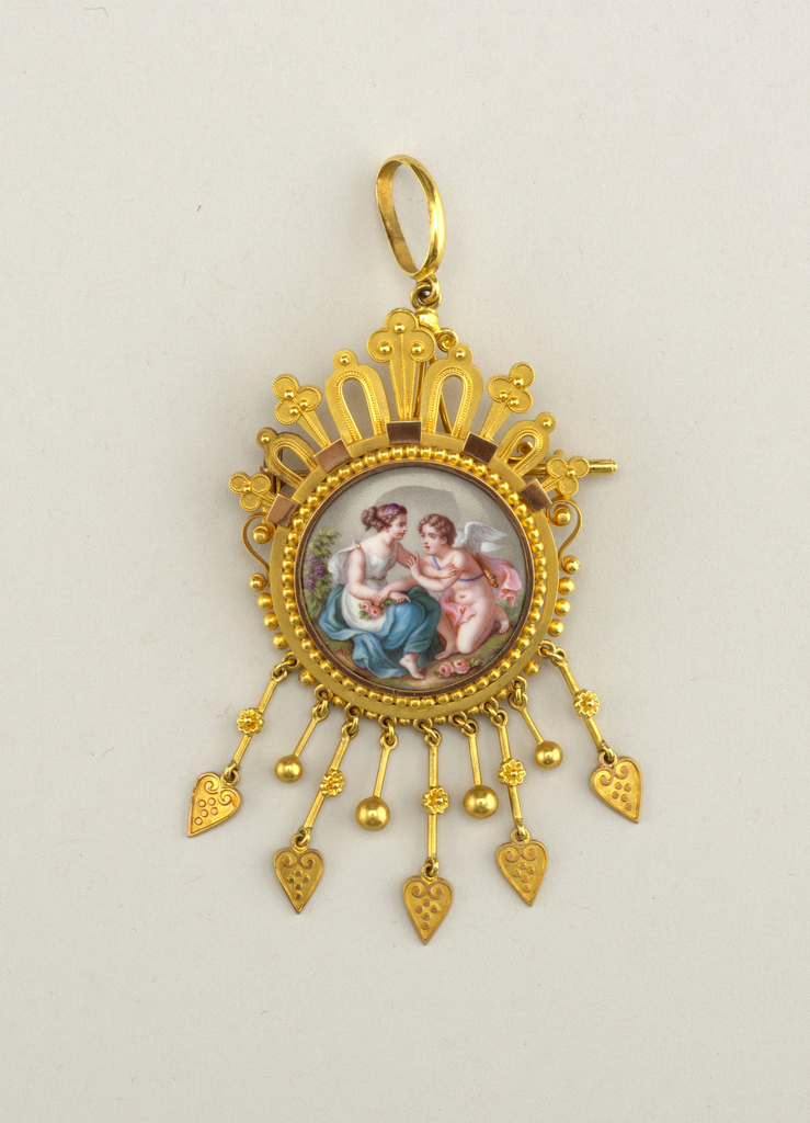 A: the brooch, with an enamel painting showing a woman with a putto in a gold frame with nine pendants of five lengths at the bottom.  The frame of the blocks is covered with blocks, balls, arches and three-lobed forms on the pendants of hearts and flowers.  B: is a sheath with ring which slips on the pin of the brooch, transforming it into a locket.  Forms a set with 1946-50-24ab.
