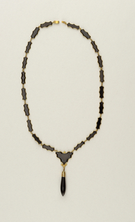 Link necklace with clasp: twenty shaped pieces of onyx set in gold and one heart-shaped piece with gold setting and ornament with ring (possibly part of a pendant now missing).  One piece of onyx is broken.