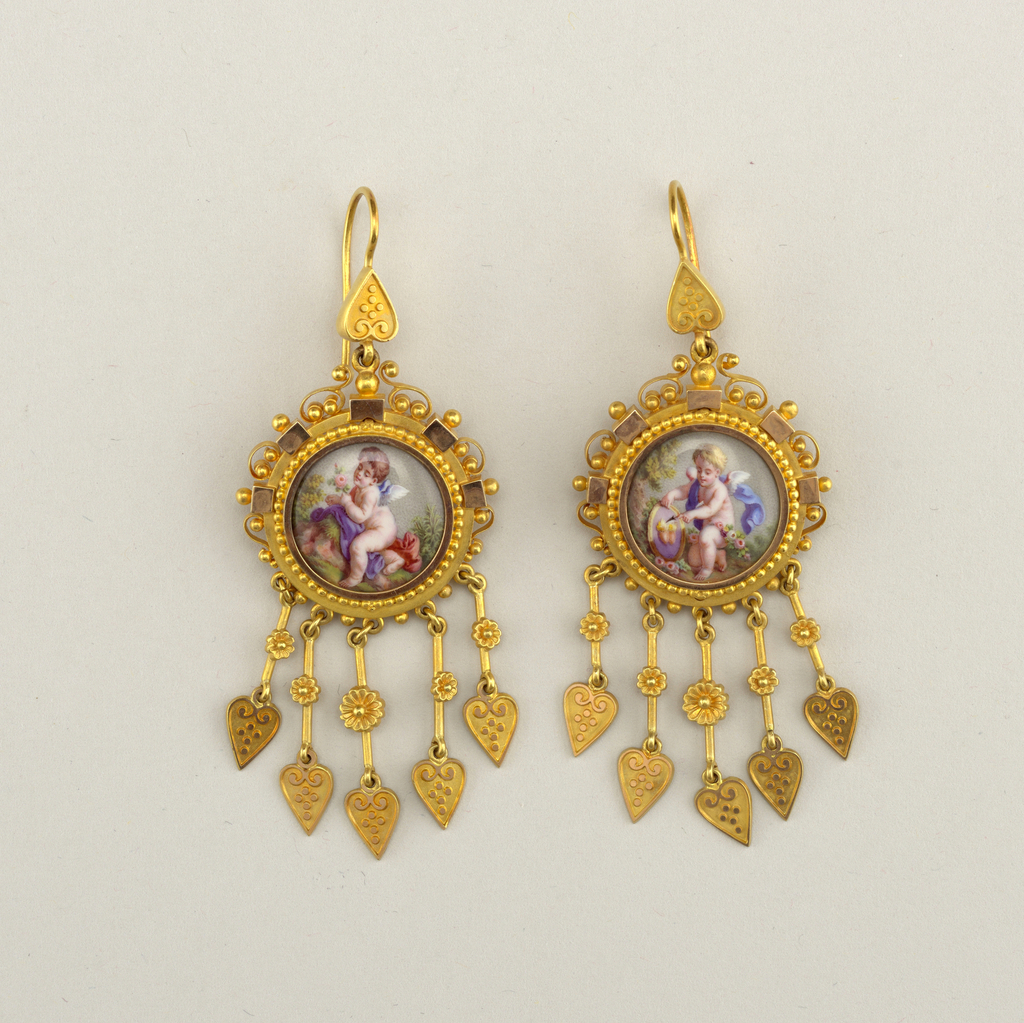 Both earrings have an enamel painting of a putto with flowers in a gold frame with five pendants of three lengths at the bottom.  The frame is covered wtih a design of blocks and scrolls with balls on the pendants, of hearts and flowers.  Forms a set with 1946-50-25.