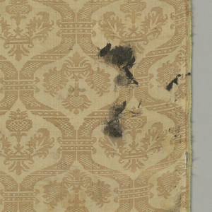 Tan damask with vertical and horizontal rows of ogives framing stylized floral forms in beige.