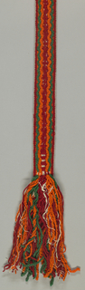 Brocaded belt in heavy wool and fine cotton in red, orange, green and white. Long fringes at each end.
