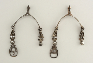 Pair of silver spurs for a woman; curved section to fit around shoe with extended piece holding rowel; chain and buckle to hold spur in place.