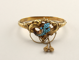 Hinged bracelet with clasp; ornament of gold scrolls with spray of turquoise and pearsl and pendant chains with vase-shaped drops.