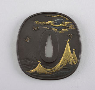 This iron tsuba is aori (oval) in shape and has a  koniku mimi (slightly raised square outer rim). Chunikubori (medium high relief) carving with Kin nunome zōgan (hatching inlaid with gold) shows a design with hoshiami (drying fish nets). Birds fly under the moon.  At the center is the nakago-ana, an opening through which the sword passes. Surrounding this is the seppadai, a flat oval area that is migaki (burnished).
