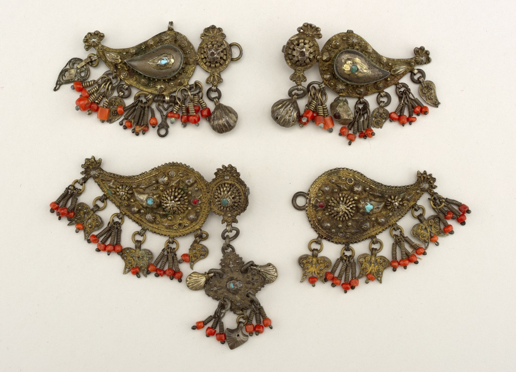 (a) Central ornament with leaf-shaped piece at either side. Raised ornaments of small pieces of turquoise and red glass; pendant ornaments of coral and silver gilt arranged in groups; (b) similar to (a) but slightly different design.