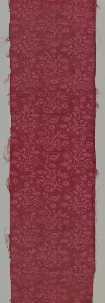 Fragment of small panel, pieced, of red silk damask.  Small pattern of flower clusters in all-over asymmetrical design.  One selvage present.