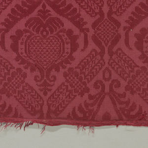 Narrow strips of a red damask in a symmetrical pattern of a lattice enclosing palmettes and foliage. Selvages present.